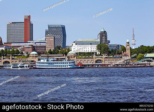 Die Landungsbrücken, das Hotel Hafen Hamburg und die Skyline Hamburgs von Elbufer gegenüber den Landungsbrücken