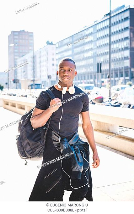 Young man walking outdoors, headphones around neck, carrying rucksack