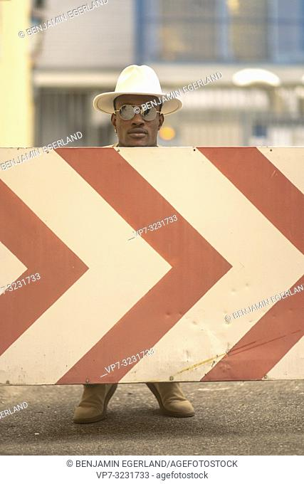 man behind arrow street sign, change of direction, Munich, Germany