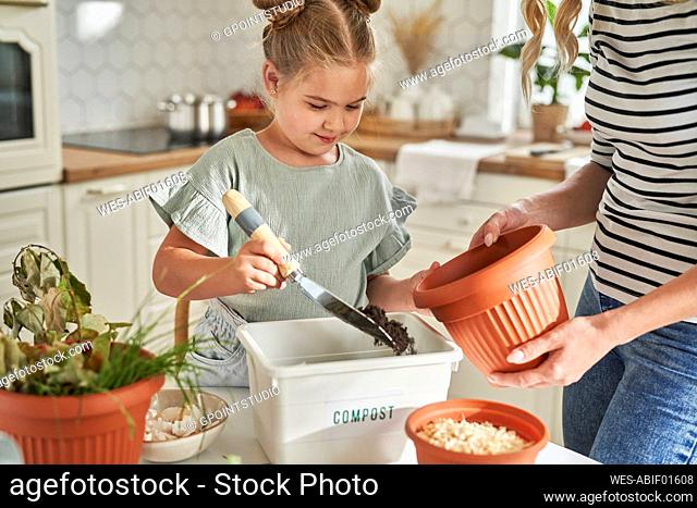 Girl filling compost in flower pot with mother at home