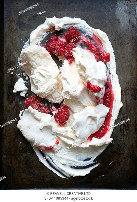 Meringue with raspberries on a baking tray