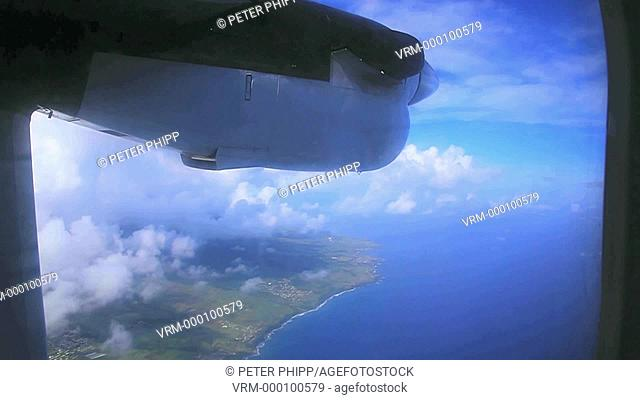 View from window from small aircraft flying over an island in Caribbean