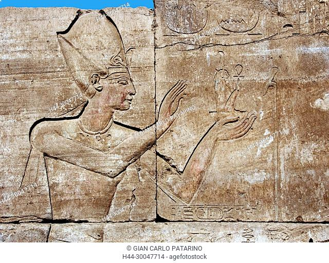 Karnak, Luxor, Egypt. Temple of Karnak sacred to god Amon: sculpture in a wall showing a pharaoh with a little statue of the goddess Maat