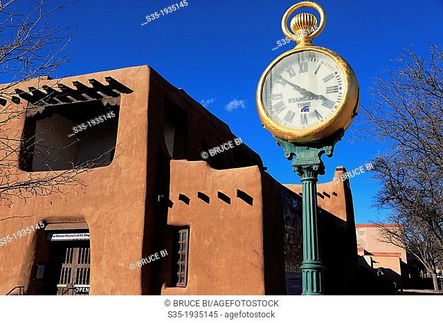 A sidewalk clock with the adobe architecture of New Mexico Museum of Art in the background. Santa Fe. New Mexico. USA