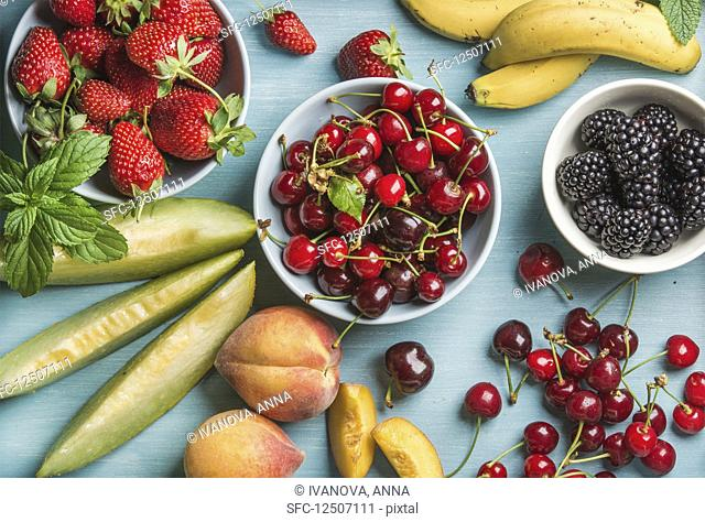 Healthy summer fruit variety - Cherries, strawberries, blackberries, peaches, bananas, melon slices and mint leaves