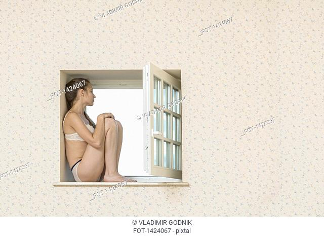 Thoughtful young woman sitting on window sill looking away