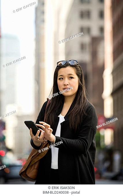 Chinese businesswoman texting on cell phone in city