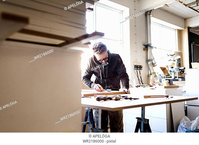 Carpenter using chisel at table in workshop