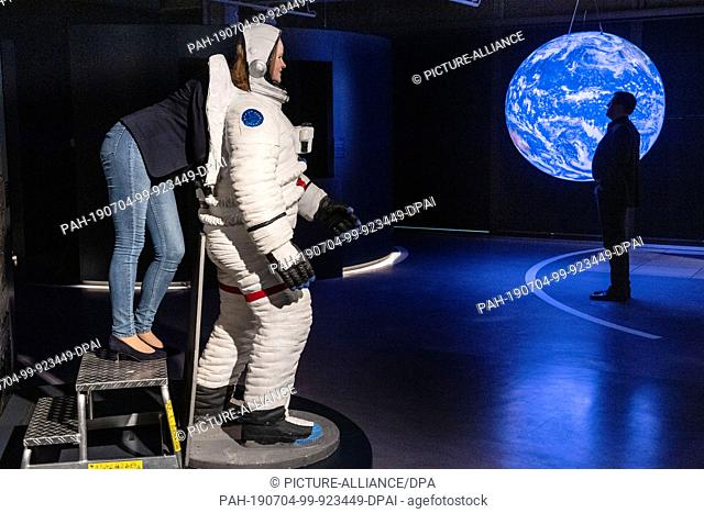 04 July 2019, North Rhine-Westphalia, Paderborn: Volunteer Lisa Flieger looks into the model of a space suit at a photo point for the visitors in the Heinz...