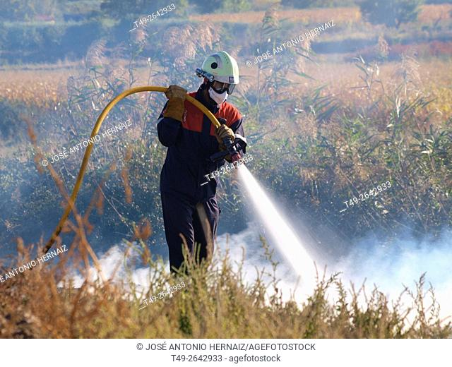 firefighter fighting against fire with a hose