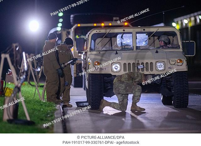 17 October 2019, Saxony-Anhalt, Burg: A female soldier of the US army refuels the military vehicle of a US brigade from Fort Hood in Texas at an improvised gas...