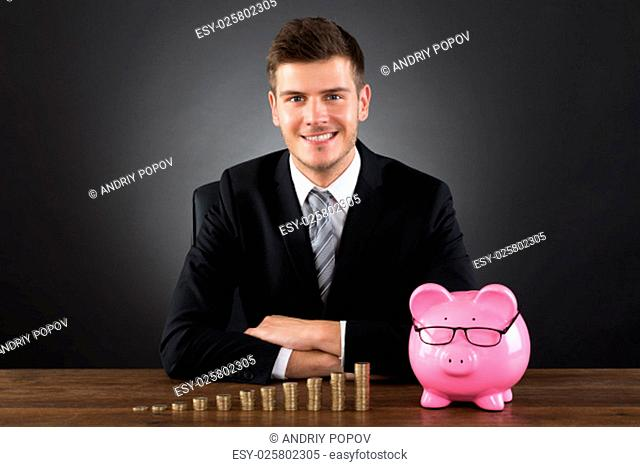 Young Businessman With Stack Of Coins And Piggybank At Desk