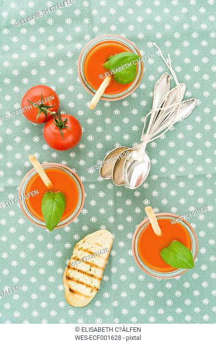 Tomato cream soup with grissini and baguette in glasses