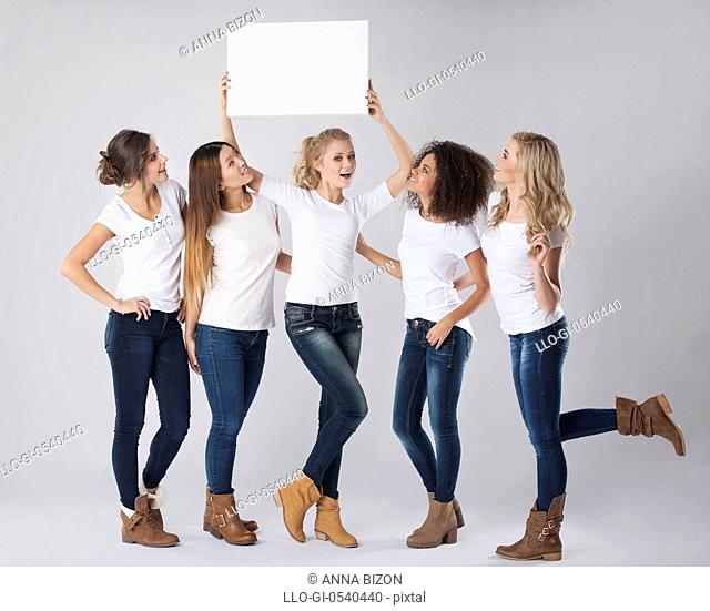 Casual girls with empty whiteboard above their heads. Debica, Poland