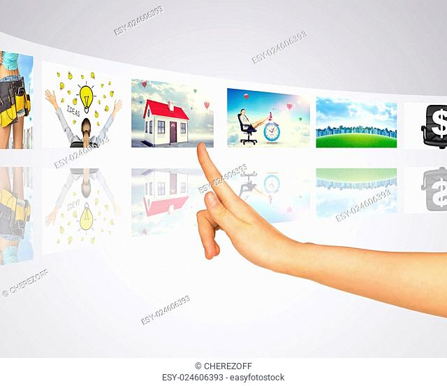 Business lady and buildings. Finger presses one of virtual screens. Mirror reflection
