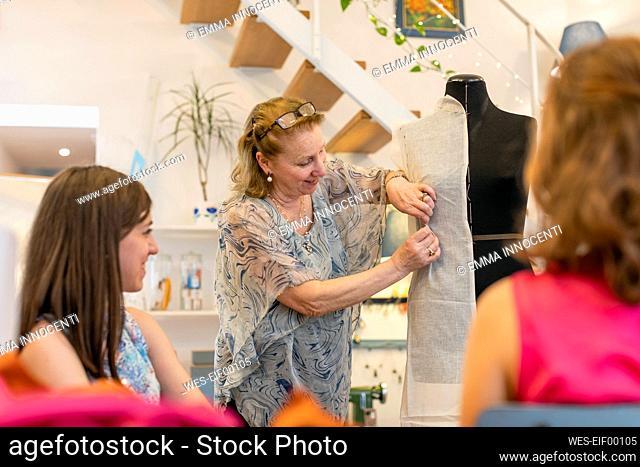 Smiling senior fashion professional showing designs on mannequin at studio