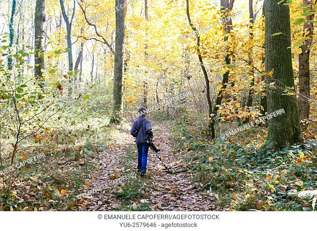 Child with metal detector in the forest in autumn