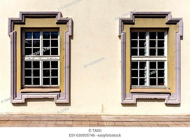 Yellow wall with two old unusual form windows