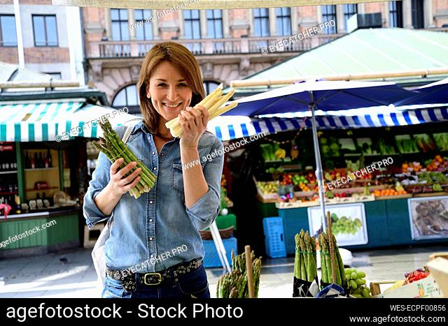 Portrait of smiling mature woman choosing asparagus at a market stall