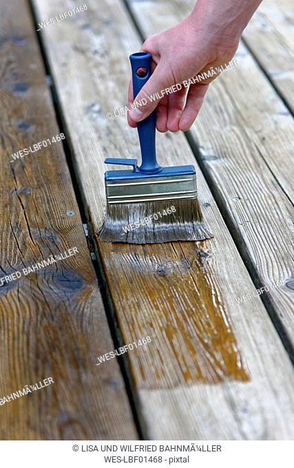 Hand applying glaze on planks, close-up