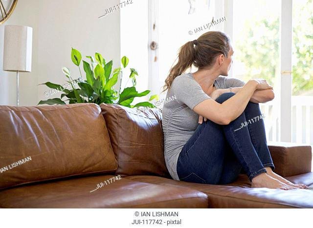 Depressed Woman Sitting On Sofa And Looking Out Of Window