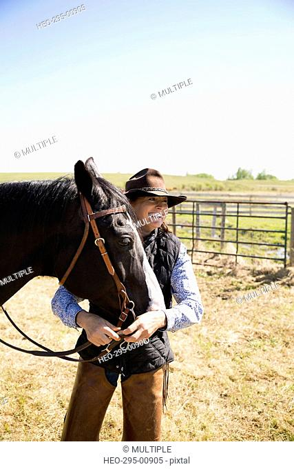 Smiling female cattle rancher with horse