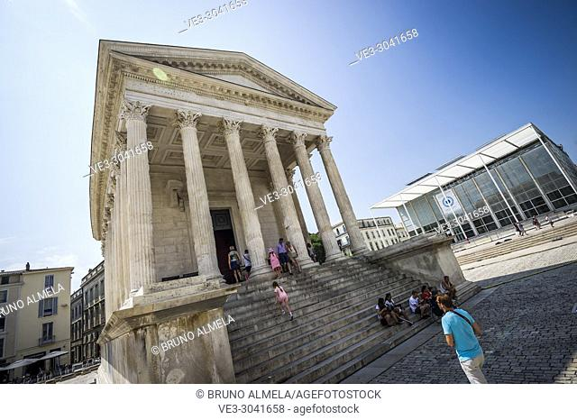Tourists visiting the Maison Carrée, a Roman temple located in Nimes (department of Gard, region of Occitanie, France)