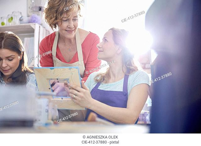 Female instructor helping student painting picture frame in art class workshop
