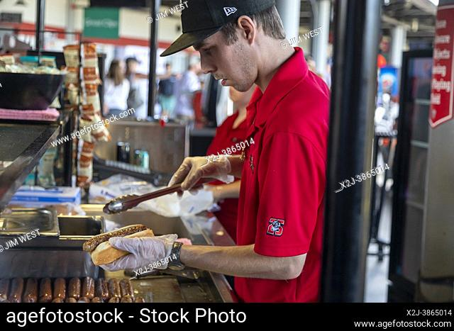Lansing, Michigan - A concessions stand worker prepares a hot dog for a customer at Jackson Field during a Lansing Lugnuts minor league baseball game