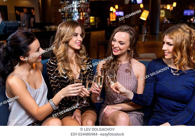 celebration, friends, bachelorette party and holidays concept - happy women clinking champagne glasses and celebrating at night club