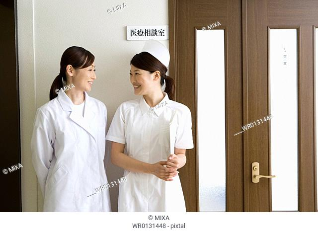 Female nurse and doctor talking in front of door