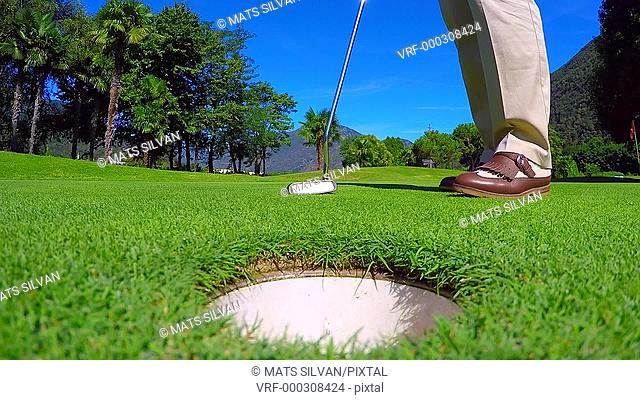Golfer Taking Up the Golf Ball from the Hole on the Green in Ticino, Switzerland