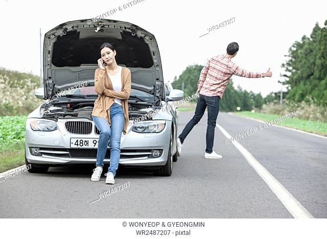 Young tired woman sitting on a broken car and a man trying to hitchhike on a road