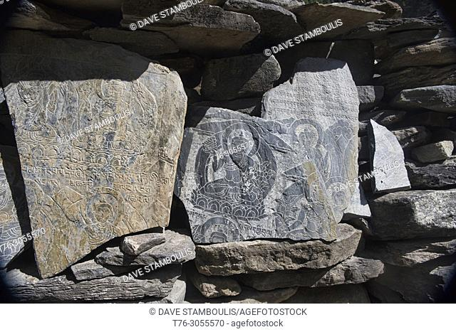 Engraved mani stones mark the entrance to the Tibetan Buddhist world on the Manaslu Circuit Trek, Nepal