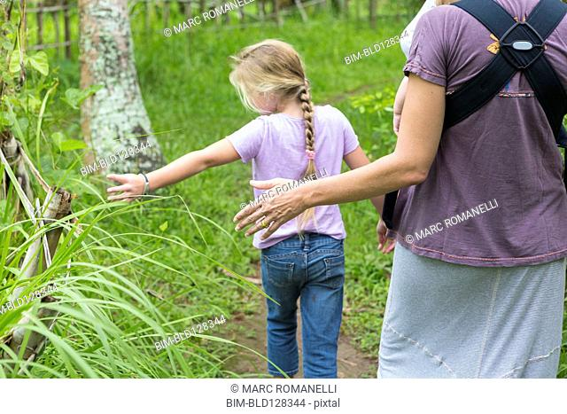 Caucasian mother and children walking in forest