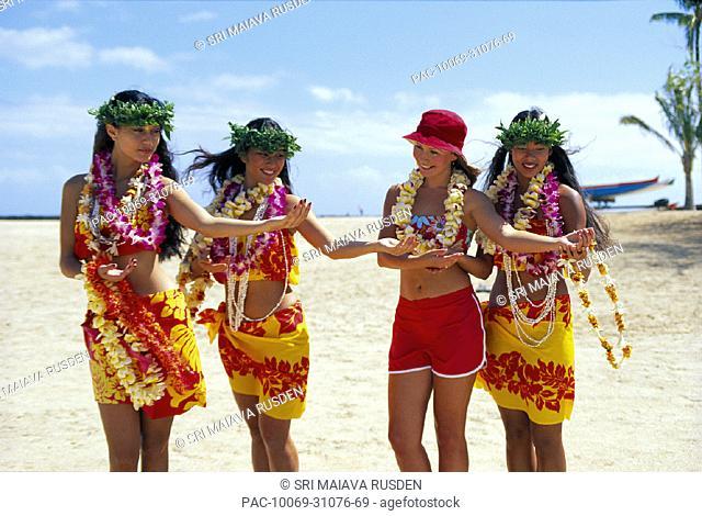 Three Hawaiian women teach visitor to dance hula, all wear leis & smiling, beach