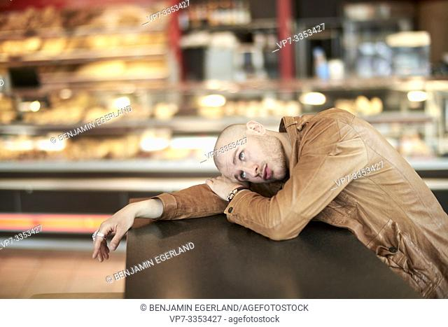 man laying on table at supermarket bakery
