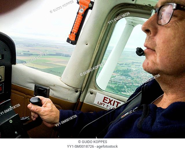 Southern Airspace, Netherlands. Mature adult male flying single prop Cessna airplane
