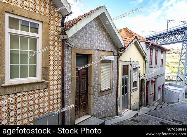 Row of small houses on Calcada da Serra street in Vila Nova de Gaia city, Portugal. Dom Luis I Bridge on background