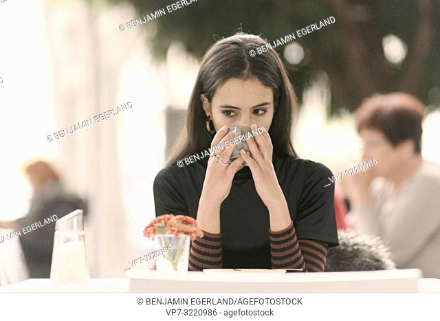 portrait of woman drinking coffee while sitting at table in café, in Munich, Germany