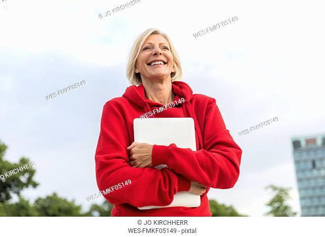 Happy senior woman wearing red hoodie holding laptop outdoors