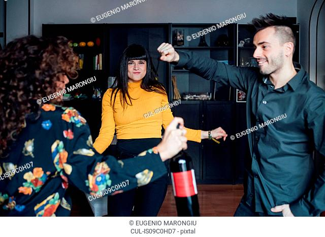 Friends celebrating, dancing at home