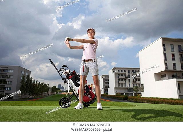 Germany, Bavaria, Munich, Young woman stretching in city-golf ground