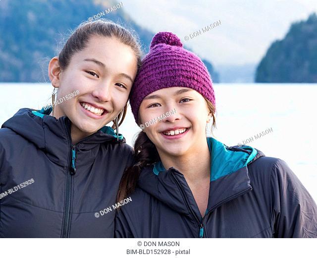 Mixed race sisters smiling at lake