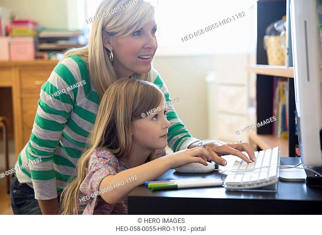 Mother and daughter using desktop computer at home