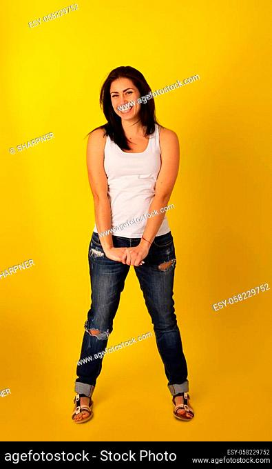 Pretty girl with dark hair in casual clothes in a good mood is standing on a bright yellow background