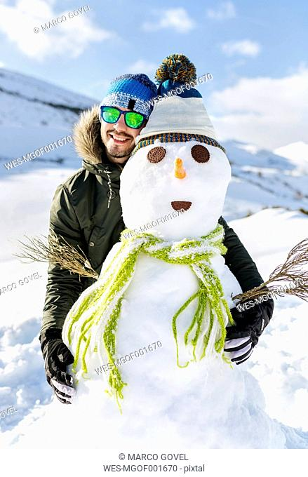 Spain, Asturias, happy young man with a snowman