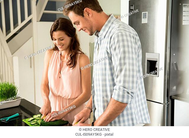 Couple cutting vegetables in kitchen