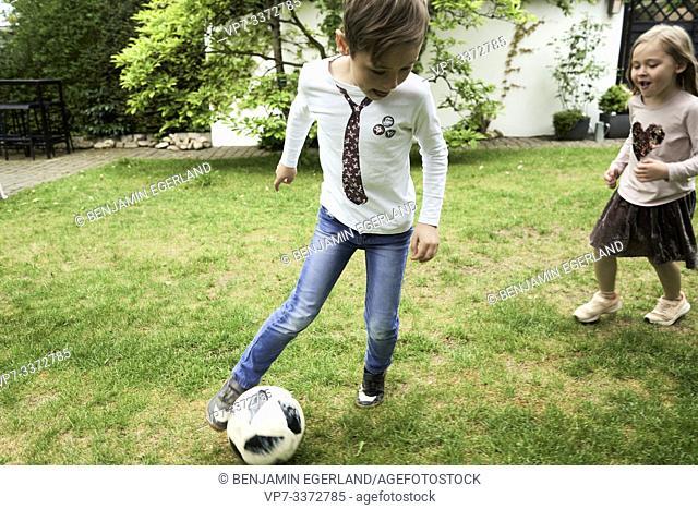 Family playing soccer in garden
