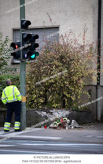 22 October 2019, North Rhine-Westphalia, Bielefeld: Candles and flowers lie at an accident site near a road, while a city employee looks at a traffic light
